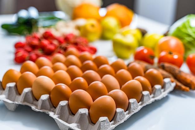 Куриные яйца в картонной коробке на столе. размытые свежие фрукты и овощи на фоне. концепция деревенской кухни.