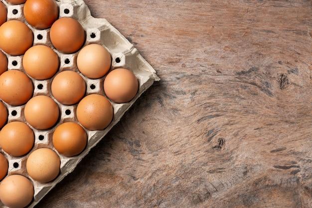 Куриные яйца в картонной коробке на фоне деревянного стола.