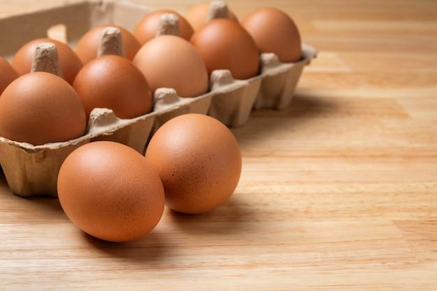 Куриные яйца в картонной коробке на деревянном столе