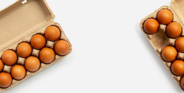 Куриные яйца в яичных коробках на белом фоне.