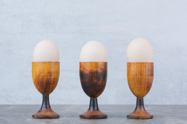 Куриные яйца в яичных чашках на мраморном фоне. фото высокого качества