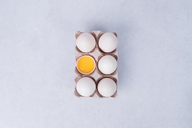흰색 표면에 종이 용기에 닭고기 달걀.