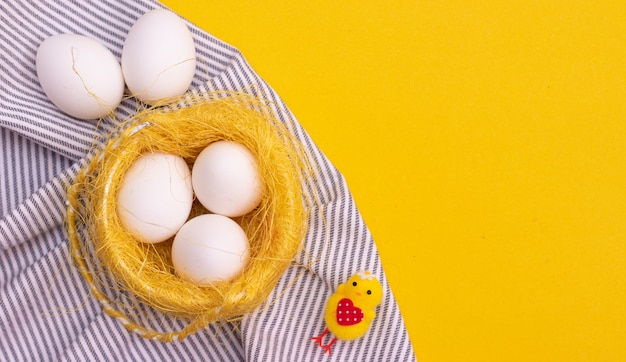 Chicken eggs on a kitchen towel on yellow