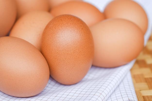 Куриные яйца лежат на белой клетчатой ткани концепции здорового питания