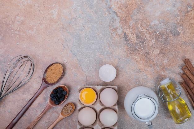 Uova di gallina, latte, olio e spezie sulla superficie di marmo.