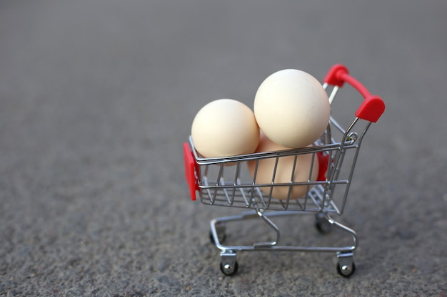 Chicken eggs in a mini shopping cart.