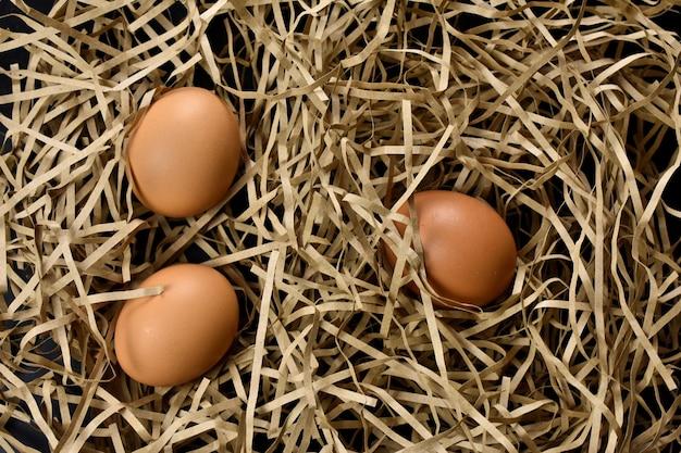 明るいわらの背景に鶏卵