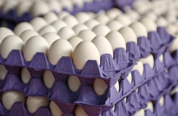 Куриные яйца на фиолетовом подносе.