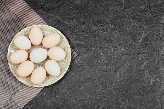 Куриные яйца на керамической тарелке. вид сверху.
