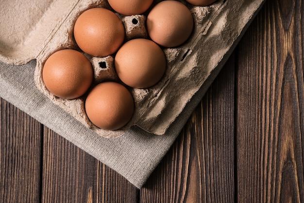 Куриные яйца на фоне деревянного стола