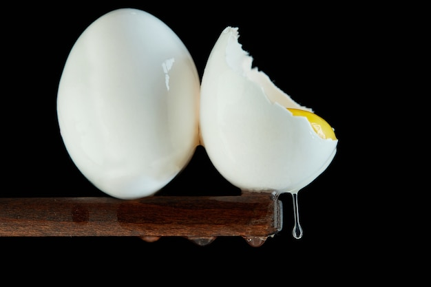 Chicken eggs, one egg is broken in which the yolk is visible and the white flows down on a black background. close up