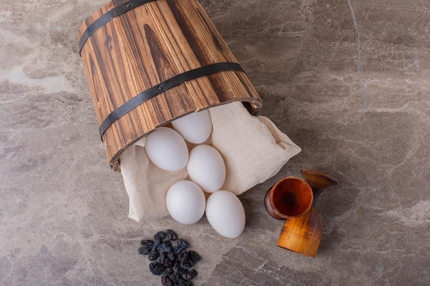 Chicken eggs out of a wooden bucket.