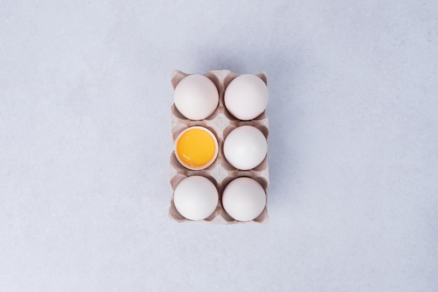 Chicken eggs in paper container on white surface.