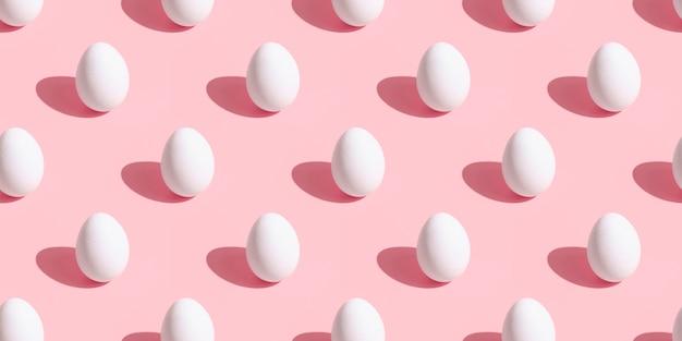 Шаблон куриных яиц на розовой поверхности