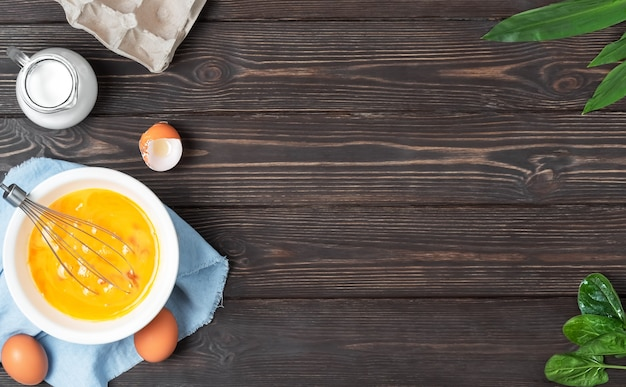 Chicken eggs in a plate with egg whisk