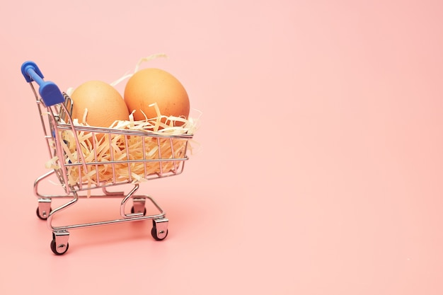 Chicken eggs in a shopping cart on a pink pastel background, copy space