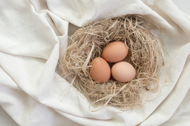 Chicken eggs in a straw nest on linen fabric