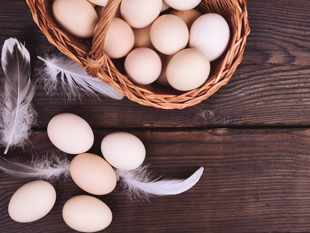 Chicken eggs in a wicker basket on a wooden brown table, top view