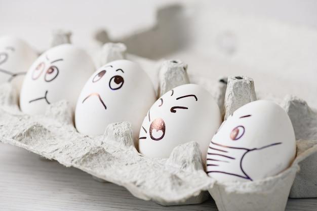 Куриные яйца с каракули лица в медицинских масках в коробке. нарисованные маркером эмоции на скорлупе белых яиц в масках из-за эпидемии коронавируса 2020 года и пасхальных праздников дома в изоляции.