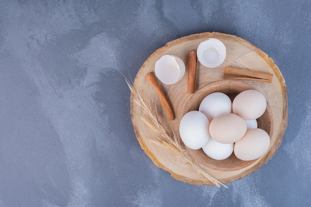 나무 접시에 달걀 껍질과 닭고기 달걀