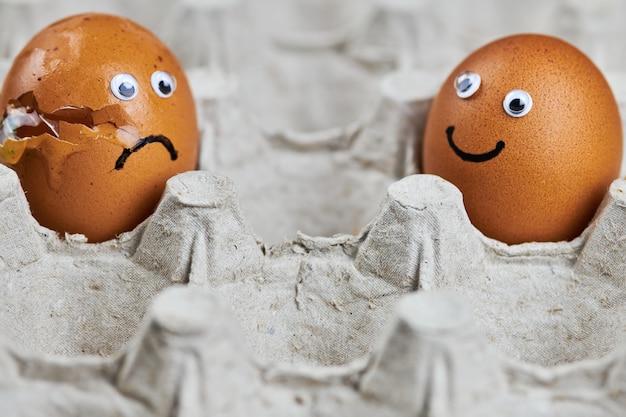 紙の卵トレイに顔と鶏の卵