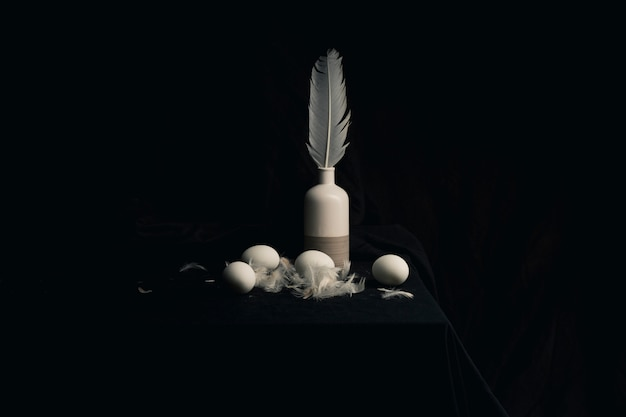 Chicken eggs with feathers near quill in vase on edge of table between blackness
