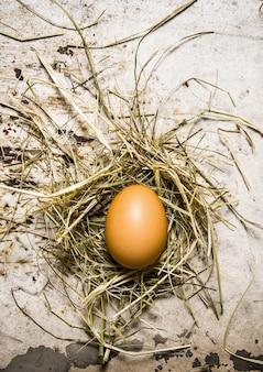干し草と鶏卵。素朴なテーブルの上。上面図