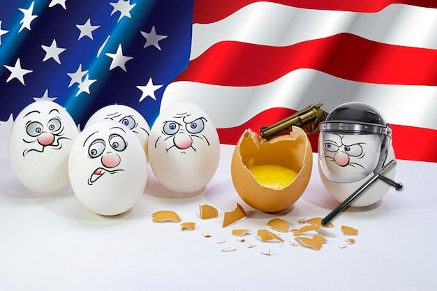 Куриные яйца с раскрашенными лицами участвуют в акции протеста на фоне флага сша. борьба за справедливость. протесты против расизма.
