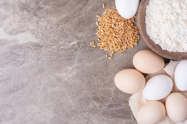 밀 곡물과 밀가루 한 컵과 닭고기 달걀