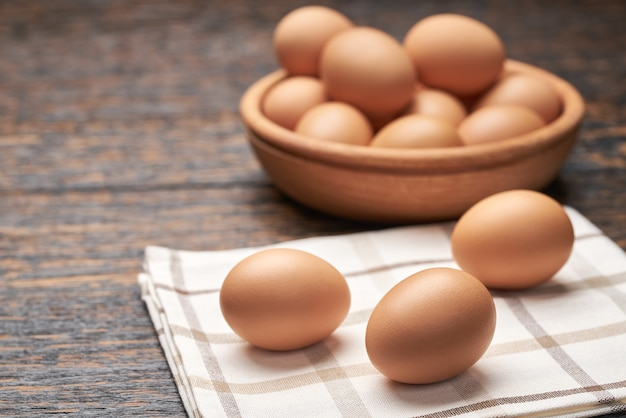 Chicken eggs in a wooden bowl on a black wooden table