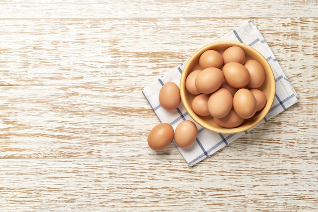 Chicken eggs in a wooden bowl on a kitchen table, top view.