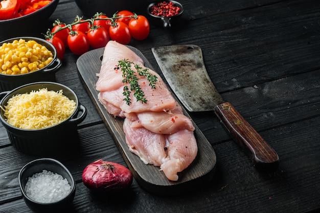 Chicken enchilada ingredients rice, mozzarella, corn, on black wooden table table