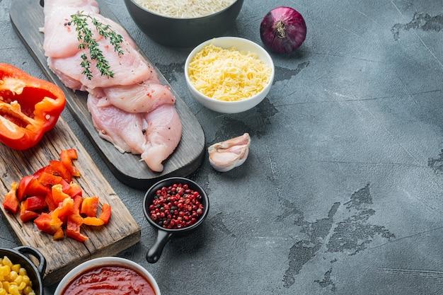 Chicken enchilada ingredients rice, mozzarella, corn, on gray table