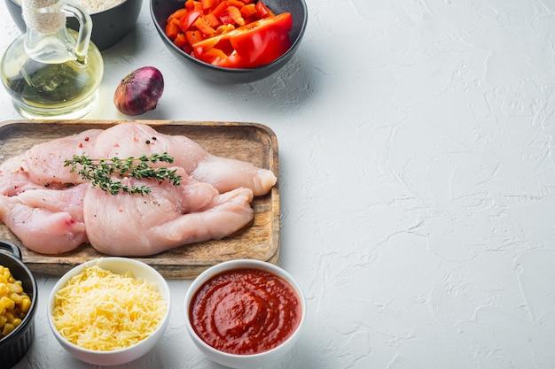 Chicken enchilada ingredients rice, mozzarella, corn, on white table