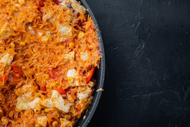 Chicken enchiladas, served in casserole, on black table, top view flat lay