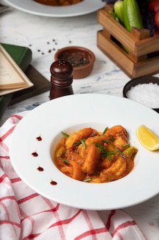 Chicken feet stew in tomato sauce in white bowl with vegetables and lemon.