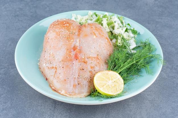 Куриное филе и лимон на синей тарелке.