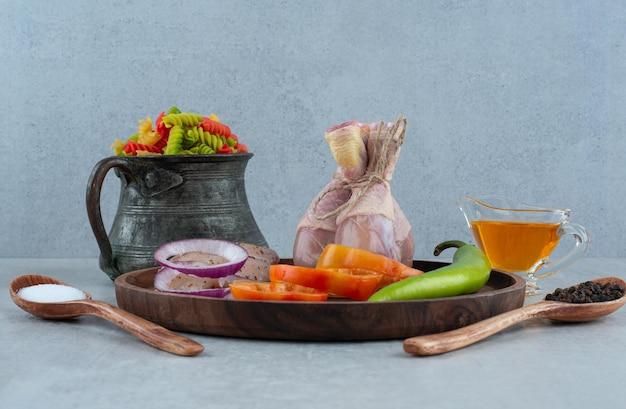 Куриное филе и овощи на деревянной тарелке с макаронами.