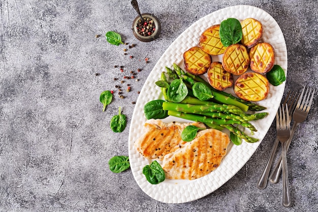 Chicken fillet cooked on a grill with a garnish of asparagus and baked potatoes.