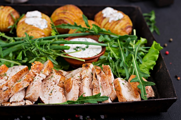 Chicken fillet cooked on a grill with a garnish of baked potatoes. dietary meal. healthy food.