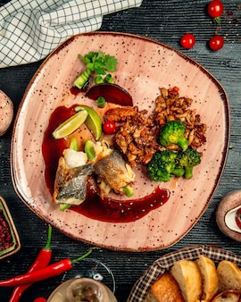 Chicken fillet rolls with nuts and green herbs and sauce inside red plate.