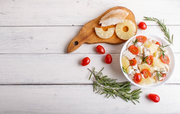 Chicken fillet salad with rosemary, pineapple and cherry tomatoes on white wooden surface.