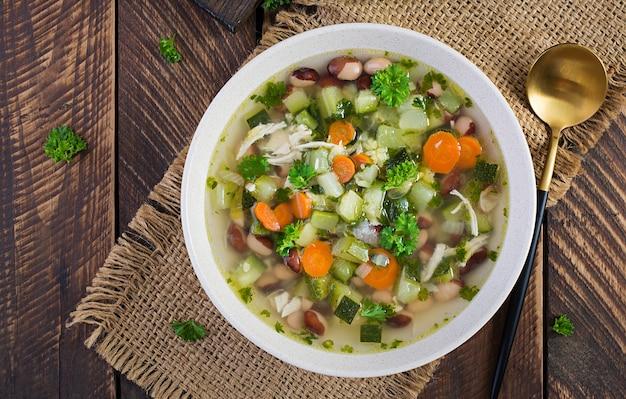 Овощной суп из куриного филе в шаре на деревянном деревенском столе. вид сверху, плоская планировка
