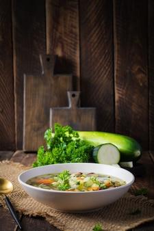 Овощной суп из куриного филе в шаре на деревянном деревенском столе.