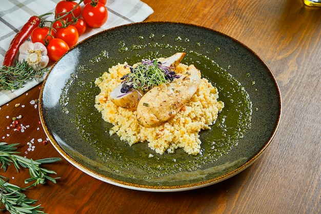 Chicken fillet with couscous garnish and pesto sauce on a green bowl on wooden table. diet fitness nutrition. healthy food. close up view