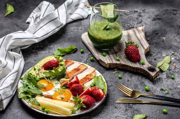 Chicken fillet with salad. healthy breakfast fried egg, avocado, strawberry, grilled chicken fillet, cheese, nuts and arugula, detox smoothie, fresh green, ketogenic diet,
