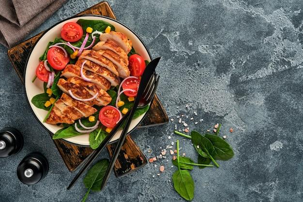샐러드 시금치, 체리 토마토, 수레 국화, 양파를 곁들인 치킨 필렛. 건강한 음식. 케토 다이어트, 다이어트 점심 개념. 흰색 바탕에 최고 볼 수 있습니다.