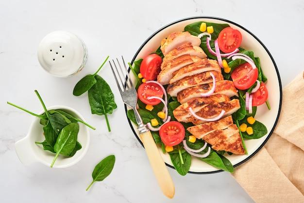 샐러드 시금치, 체리 토마토, 수레 국화, 양파를 곁들인 치킨 필렛. 건강한 음식. 케토 다이어트, 다이어트 점심 개념. 흰색 표면에 최고 볼 수 있습니다.