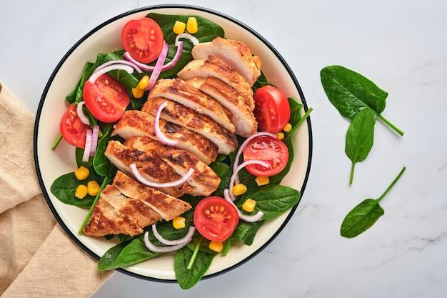 샐러드 시금치, 체리 토마토, 수레 국화, 양파를 곁들인 치킨 필레