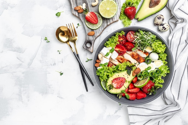 Chicken fillet with salad with avocado, feta cheese, quail eggs, strawberries, nuts and lettuce on white background. healthy food, keto diet, diet lunch concept. top view.
